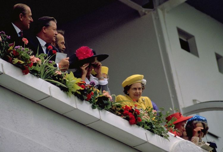 The Queen at Derby Day 1988. Queen Elizabeth II attended the 1988 Epsom Derby horse race at Epsom Downs on Wednesday, June 1st with her daughter Princess Anne in matching yellow. The 209th running of the Derby was won by Kahyas, ridden by Ray Cochrane and trained by Luca Cumani. The Royal Family can be seen here really focused on their love of horses and probably the antics of the general public in the stands below them. http://pics.travelnotes.org At The Races Binoculars British Derby Day Duke Of Edinburgh Epsom Downs Faces Family Flowers Hats Her Majesty Horse Racing Michel Guntern People Prince Philip Queen Elizabeth  Royal Box Royal Family The Queen Tradition Travel Travel Photography Travel Photos Travel Pics Snap A Stranger