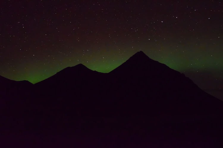 Low angle view of silhouette mountain against sky at night
