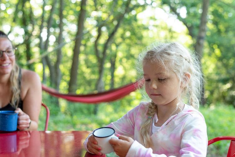 Girl holding ice cream cone against trees