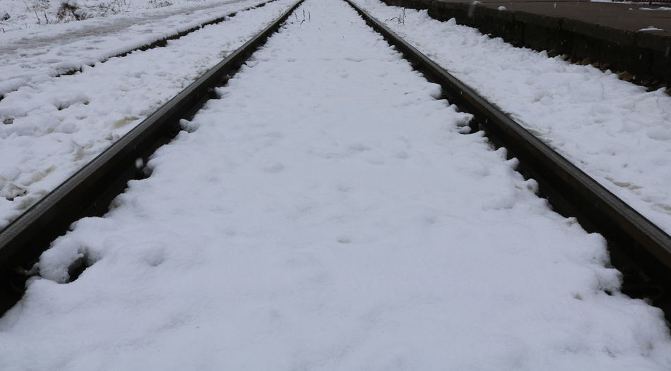 Snow covered railroad tracks on snowcapped field