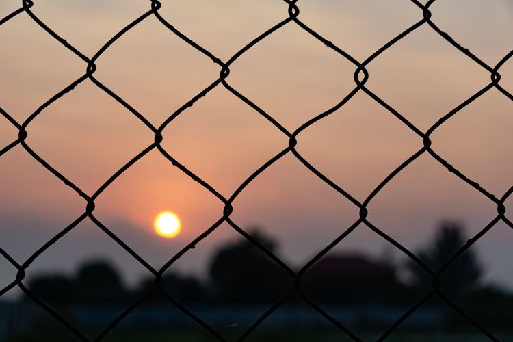 Sunset behind the chainlink fence. Tranquility Twilight Barrier Beauty In Nature Boundary Chainlink Fence Dusk Evening Evening Sky Fence Focus On Foreground Metal Nature Orange Color Outdoors Protection Safety Scenics - Nature Security Silhouette Sky Sun Sunset Tranquil Scene Twilight Sky