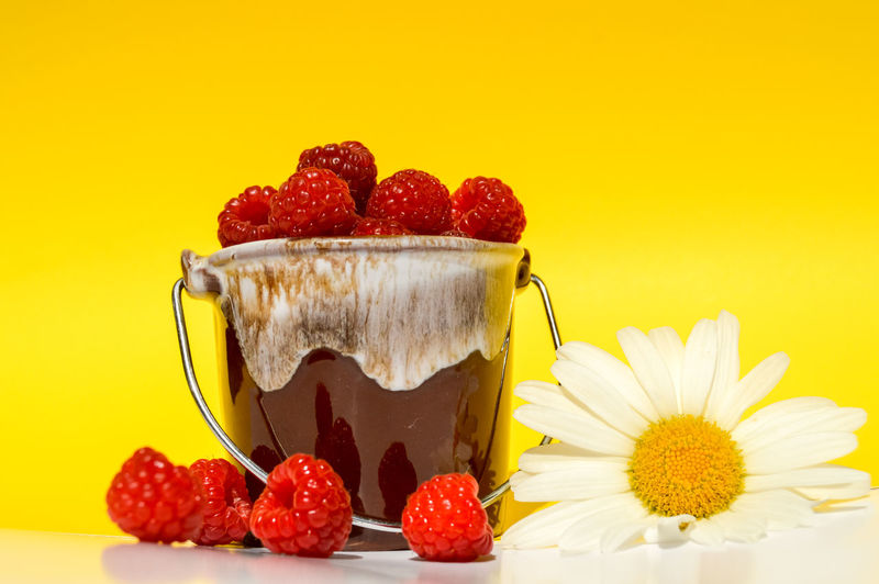 Close-up of strawberries in container against yellow background