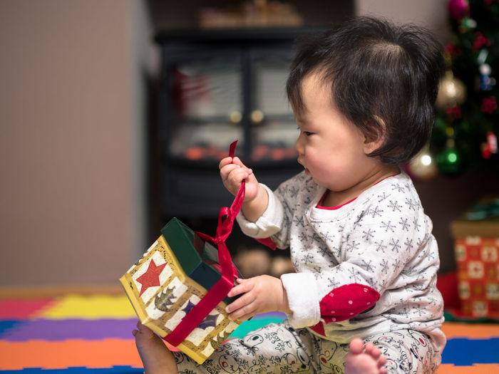 Close-up of baby girl unwrapping christmas gift