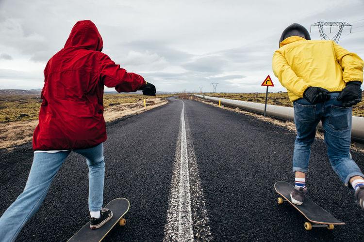 Full length of couple skateboarding on road against sky