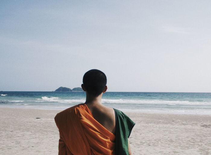 Rear view of monk standing on beach against clear sky