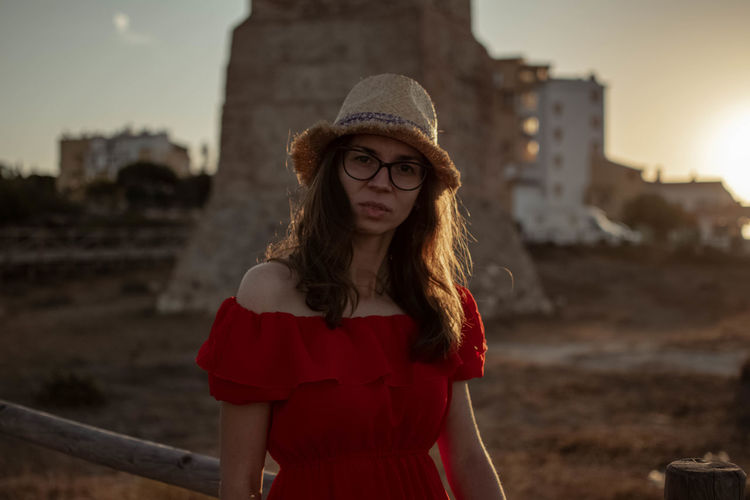 Portrait of woman standing in city against sky