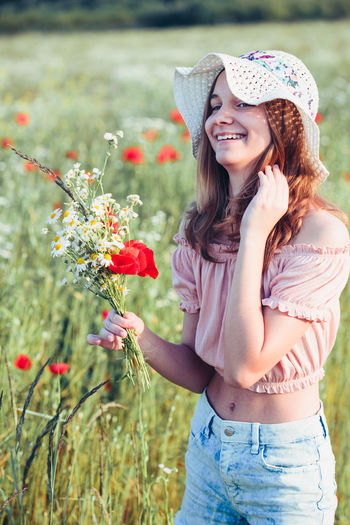 Beautieful young girl in the field of wild flowers. Teenage girl picking the spring flowers in the meadow, holding bouquet of flowers. She wearing hat and summer clothes. Spending time close to nature Girl Beautiful Woman Young Teenager Flowers Bouquet Hat Summer Beauty Nature Natural Happy Smile Wild Field Meadow Pick Picking Spring Springtime Blooming Blossom Real person