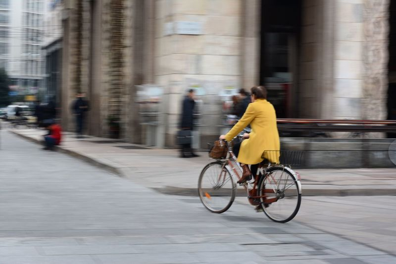 Women riding bicycle on city street