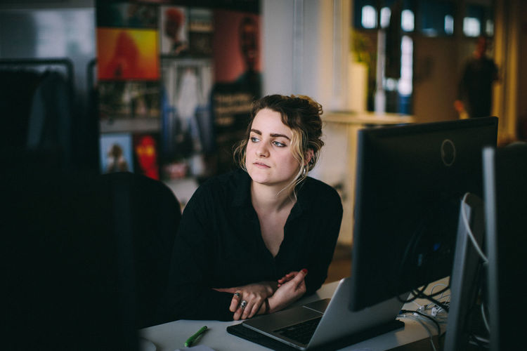 Young woman looking away while sitting by laptop on table at office