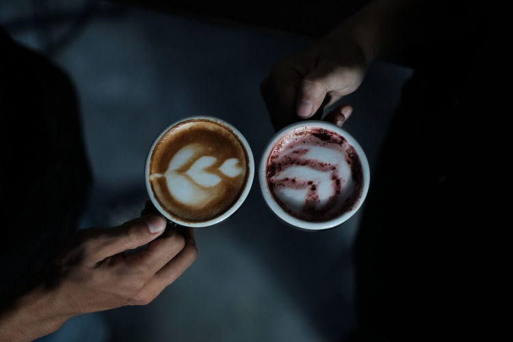 Two people hold coffee latte