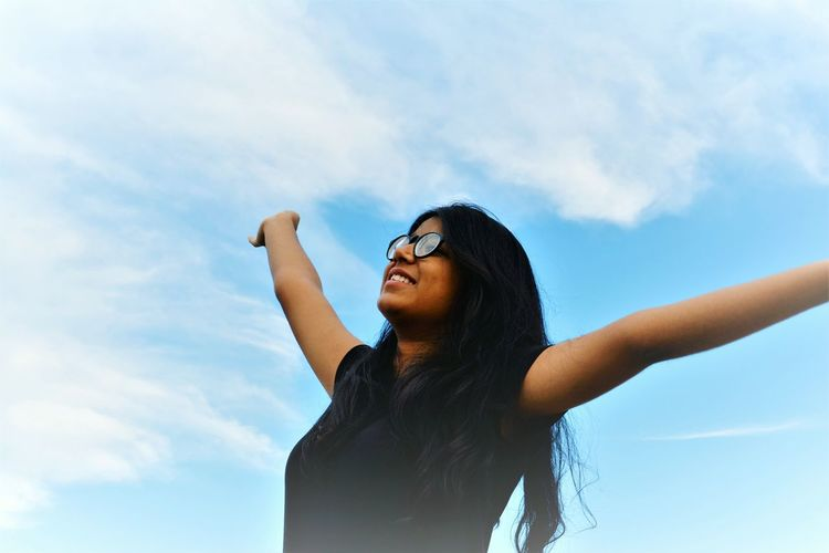 Low angle view of young woman with arms outstretched standing against sky