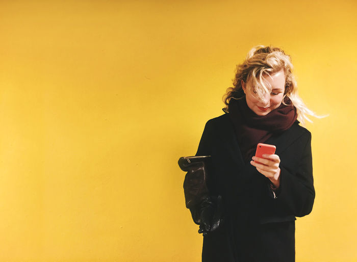 Happy Beautiful Woman Using Phone Against Yellow Background
