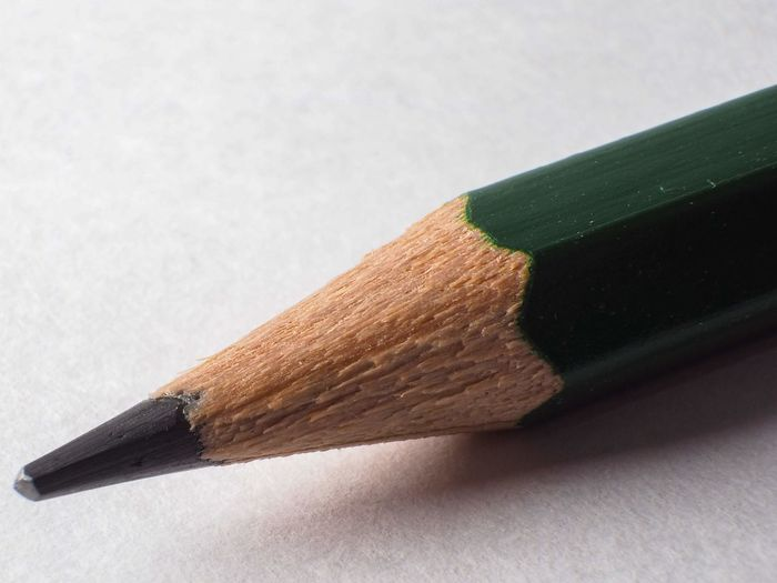 Close-up of green wood pencil on table against white background