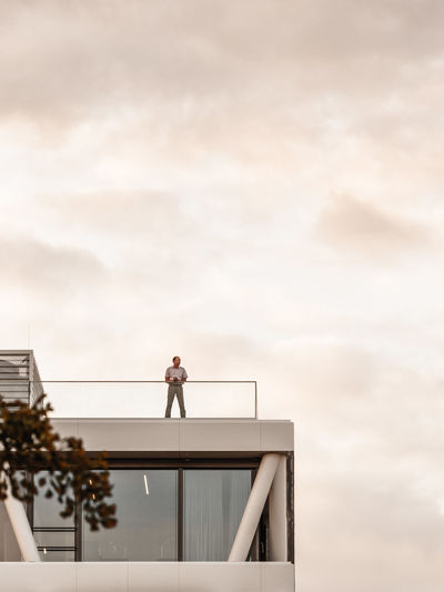 Low angle view of man standing at terrace against sky