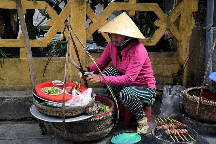 Street food lady prepares skewers in Hoi An, Vietnam Adult Adults Only Agriculture Asian Street Food Asian Street Kitchen Day Farmer Hoi An, Vietnam Occupation One Person One Woman Only Only Women Outdoors People Rural Scene Street Food Vendor In Hoi An Street Food Vietnam Vietnamese Lady Prepares Food Vietnamese Skewers Women Working