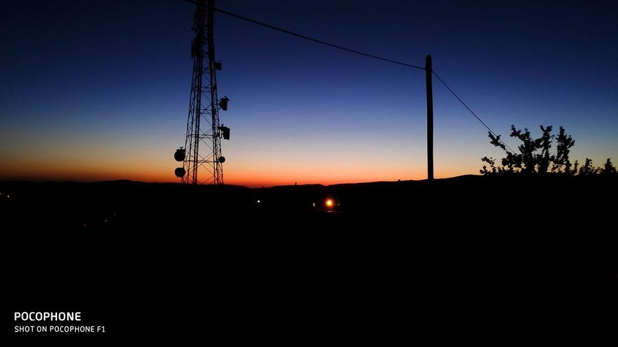 Silhouette of electricity pylons against clear sky during sunset