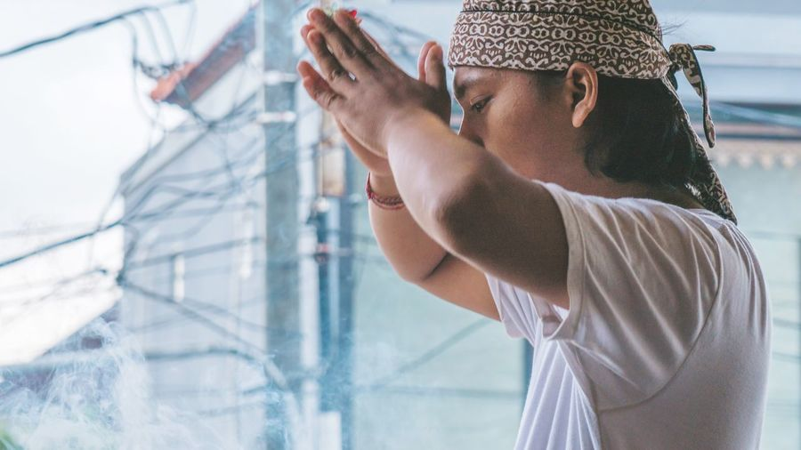 Side view of man praying while standing against building
