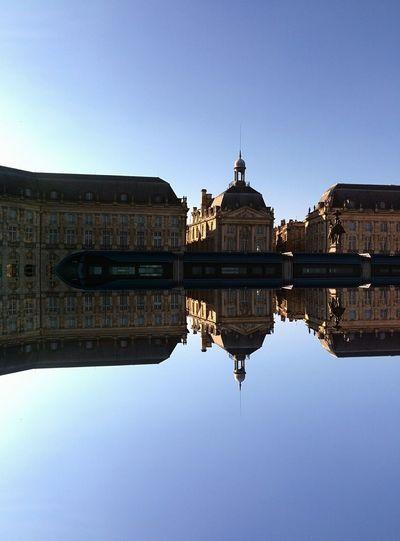 Place de la bourse reflecting in miroir d eau against clear sky
