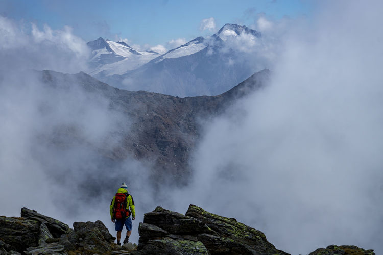 Rear view of person with backpack standing on mountain against sky