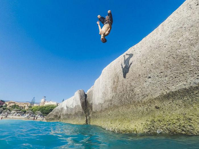 Boy jumping in sea against blue sky