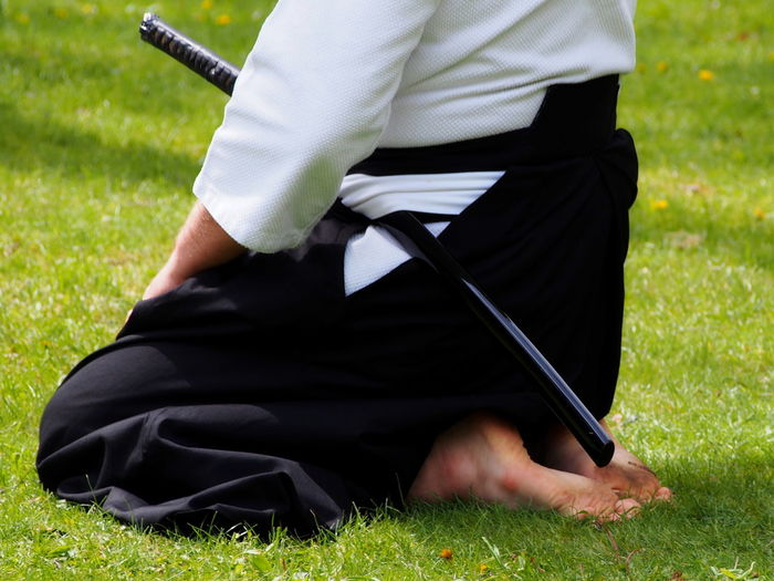 Low section of man with samurai sword on field
