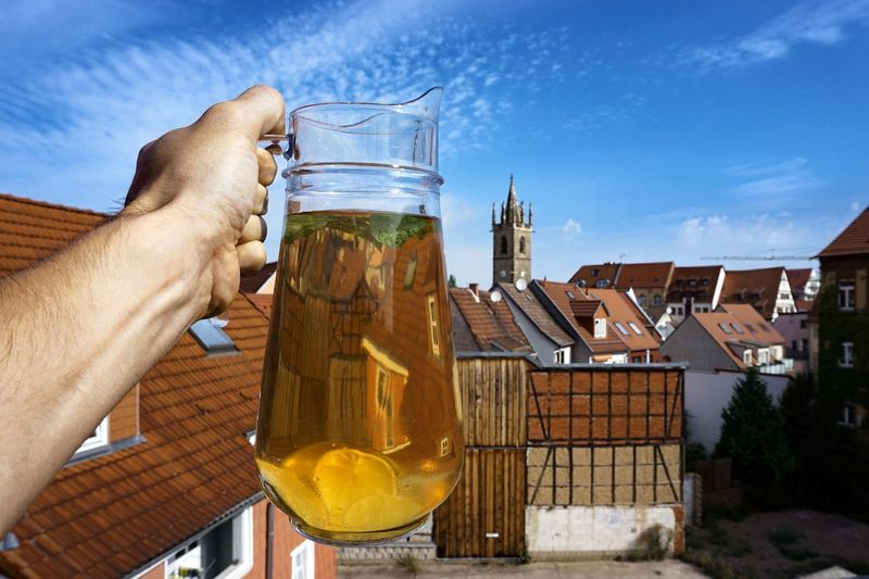 Cropped image of hand holding beer glass against sky