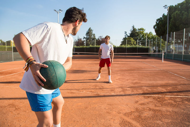Tennis Players Exercising With Medicine Ball At Court
