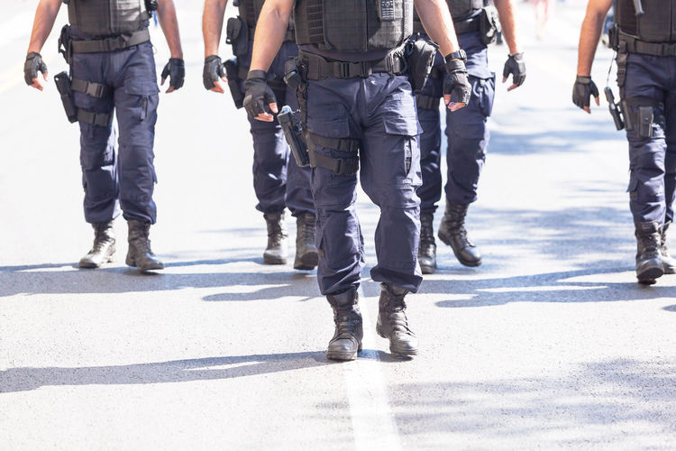 Unrecognizable armed police officers on duty Terrorism Brutality Cops Safety Protect Protection Uniform Order Law Enforcement Security Police Officer Policemen Armed Police Armed Armed Forces On Duty Patrol  Police Patrol Police Force Police Motion Real People Street Walking Group Of People