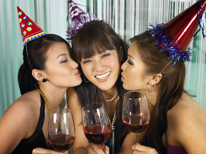Female friends kissing young woman in party