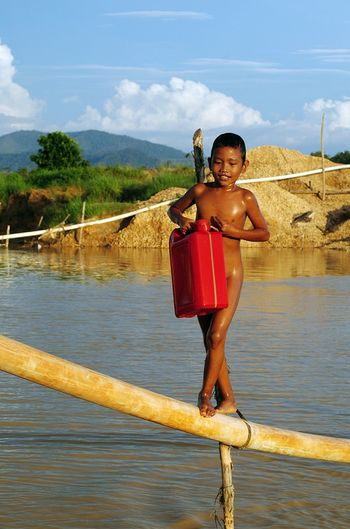 Naked boy with can walking on bamboo over lake