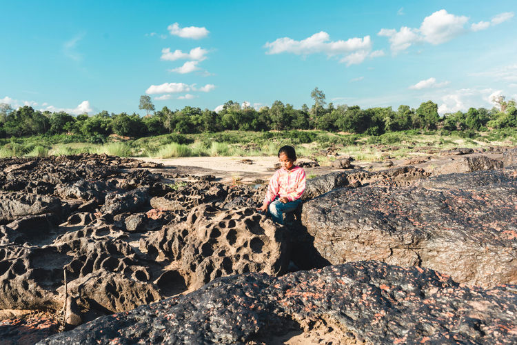 Full length of teenage girl standing on rock