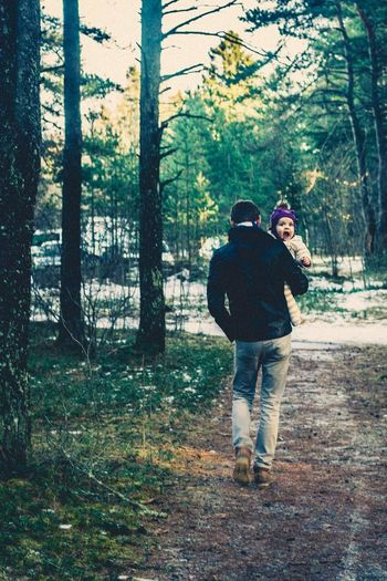 Rear view of father carrying cute son while walking on footpath at forest