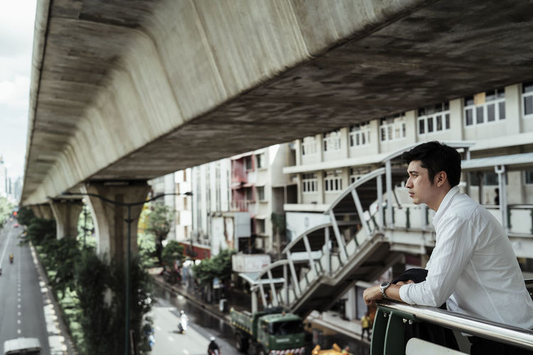 Side view of young man sitting on railing