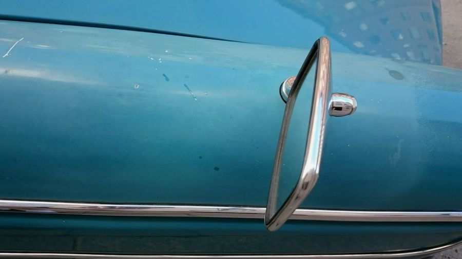 Blue car detail with rear-view mirror
