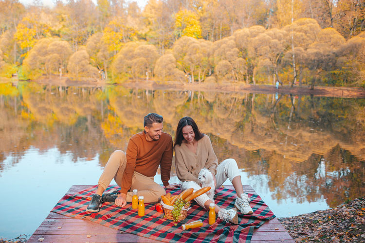 Rear view of couple sitting on rock during autumn