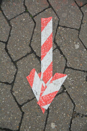 High angle view of arrow symbol on footpath