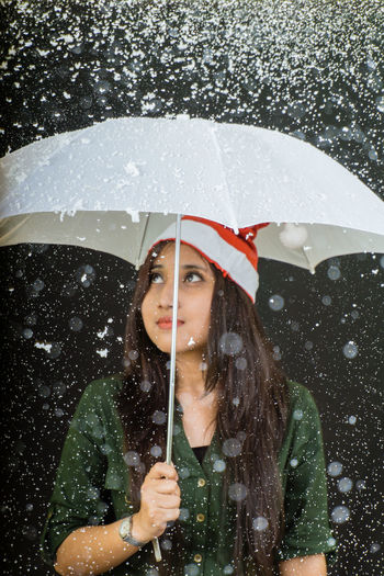 Young woman with umbrella during snowfall against black background