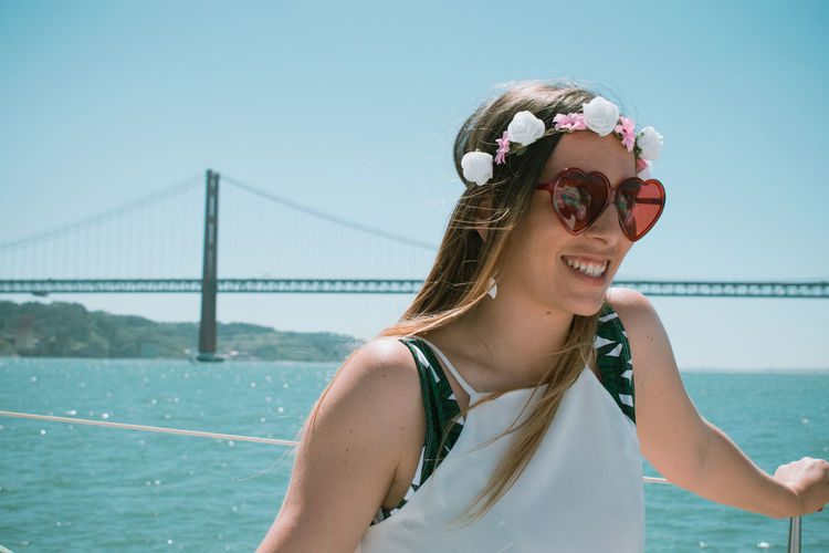 Smiling young woman wearing sunglasses standing against clear sky during sunny day