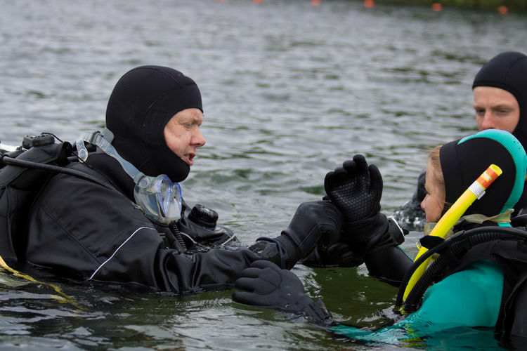 Man Assisting Woman For Wearing Gloves While Swimming In Sea