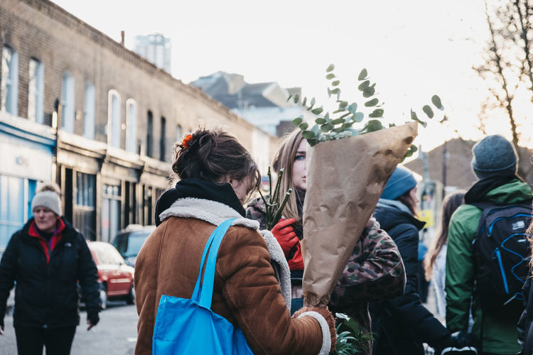 People walking with plants and flowers purchased at the Columbia Road Flower Market, a street market in East London that is open every Sunday. London Uk East London City City Life Weekend Activities Winter Day Columbia Road Flower Market Flowers Market Street Market Leisure Activity Recreational Pursuit Flowers Plants Shopping London lifestyle Real People Incidental People Purchases Sunday Market London Life Everyday Lives