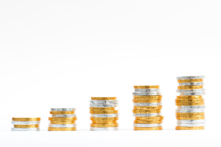Gold and silver coins piled up on an isolated white background to make the shape of an upwards graph. Arrangement Cash Coins Finance Financial Gold Gold Coins Golden Graphic Higher In A Row Lots Money Positive Savings Side By Side Silver  Silver Coin Stacks  Studio Shot Upwards White Background