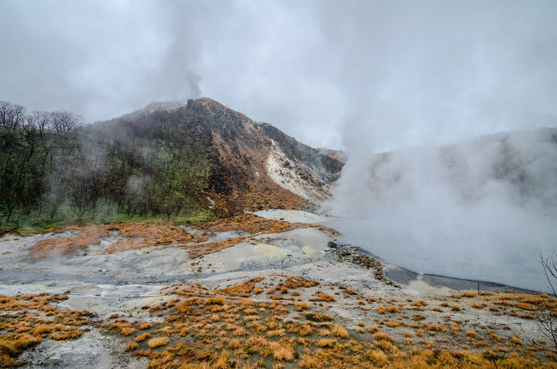 Scenic view of mountain by hot spring against sky