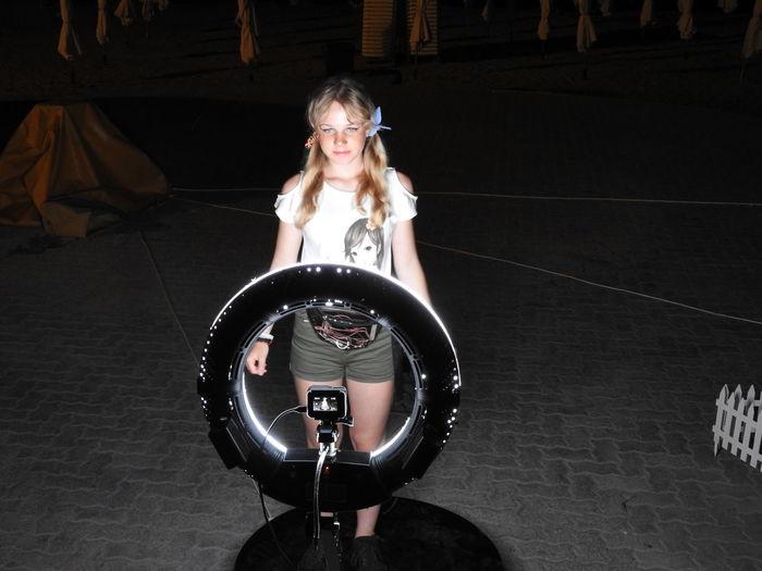 Smiling girl standing against illuminated camera at night