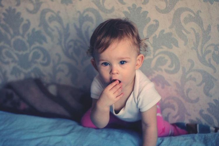 Baby girl on bed at home