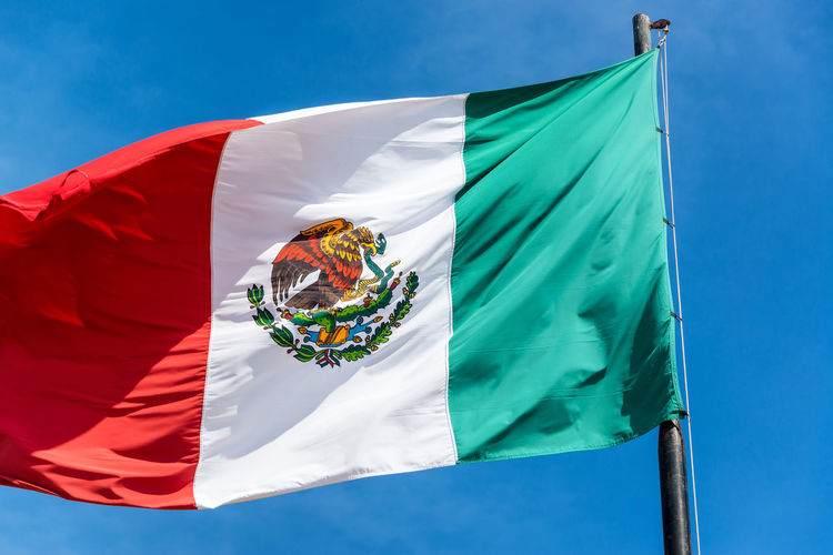 Closeup view of a Mexican flag waving in the wind as seen in Izamal, Mexico City Country Izamal Yucatan Mexico National Patriotic Travel View Yúcatan America Closeup Culture Flag Fluttering Izamal Outdoors Patriotism Street Symbol Tourism Town Waving Wind Yucatan Mexico Yucatan Peninsula