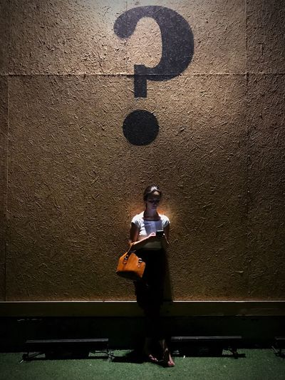Woman using phone while standing below question mark on wall at night