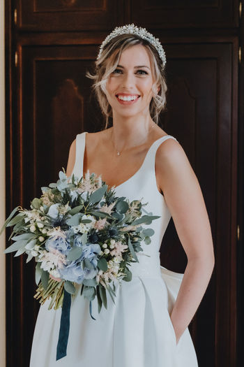 Portrait of bride holding bouquet standing against wall