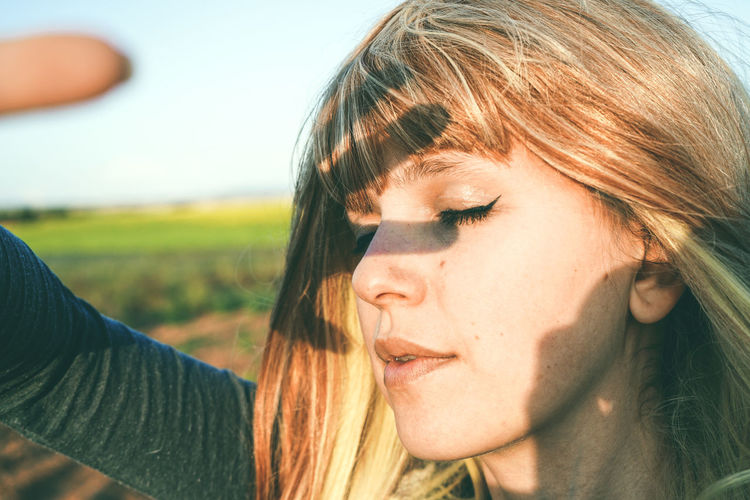 Close-up of young woman shielding eyes while standing at field against sky on sunny day