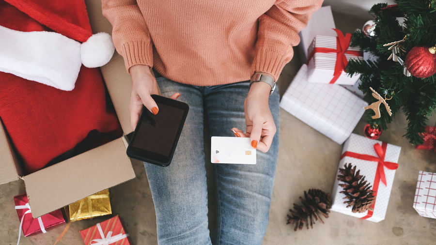 Midsection of woman holding credit card while using phone