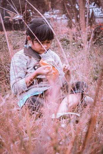 Full length of a girl holding plant